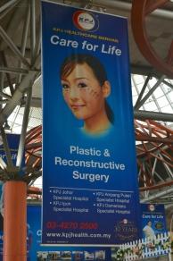 Malezja, Kuala Lumpur, reklama operacji plastycznych na dworcu kolejowym