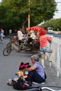 Chiny, Pekin, przed Jingshan Park, riksze i uliczna sprzedawczyni pamiątek