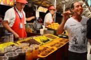 Chiny, Pekin, Night Market na Donghuamen Street, facet próbujący skorpiona