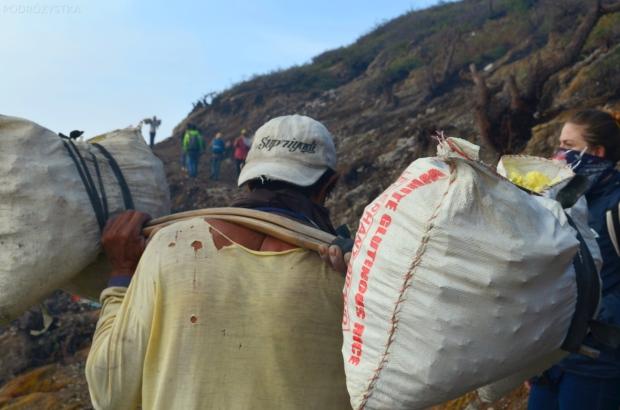 Indonezja, wyspa Java, wulkan Ijen, w workach górnicy dźwigają mniejsze kawałki siarki
