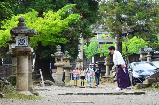 Japonia, Kyoto, mężczyzna kłania się w stronę odjeżdżającego samochodu swoich gości