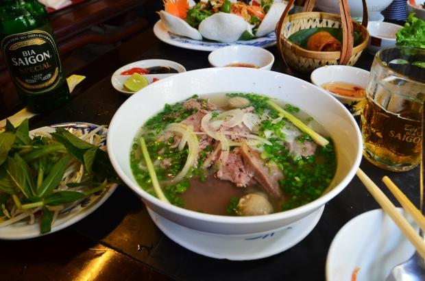 Wietnam, Ho Chi Minh City (Sajgon), na pierwszym planie tradycyjna zupa Pho, w tle sajgonki i sałatka, jest i piwo!